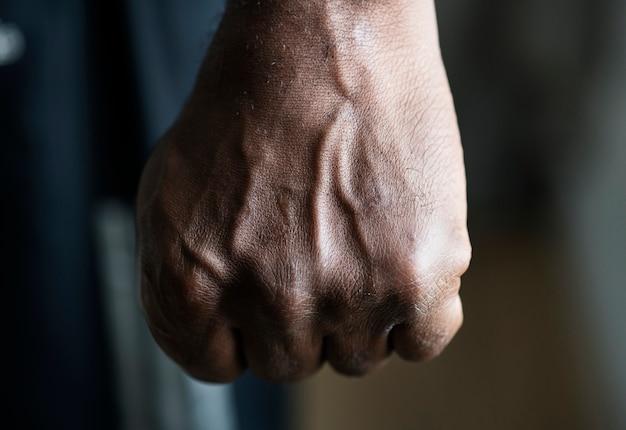 Primo piano di una mano nera in pugno Foto Gratuite
