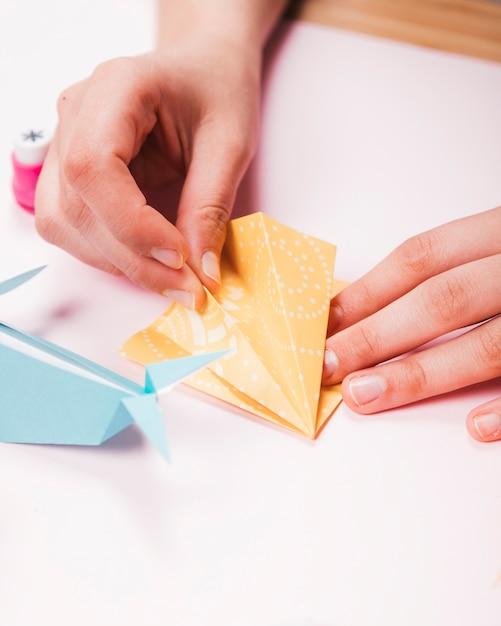 Primo piano di una mano umana che fa uccello di origami Foto Gratuite