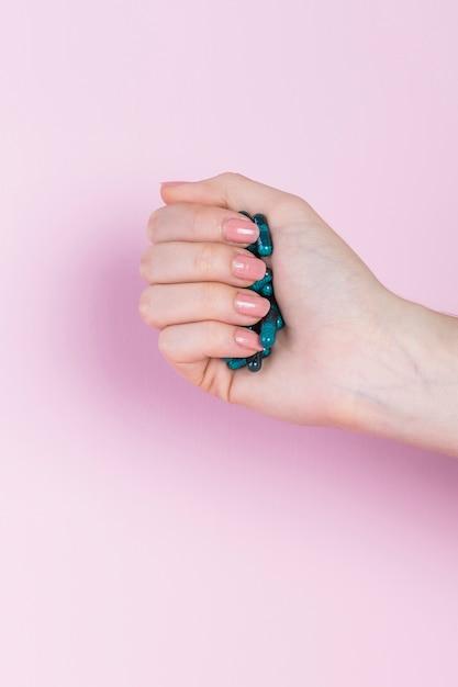 Primo piano di una mano umana che tiene capsula verde Foto Gratuite