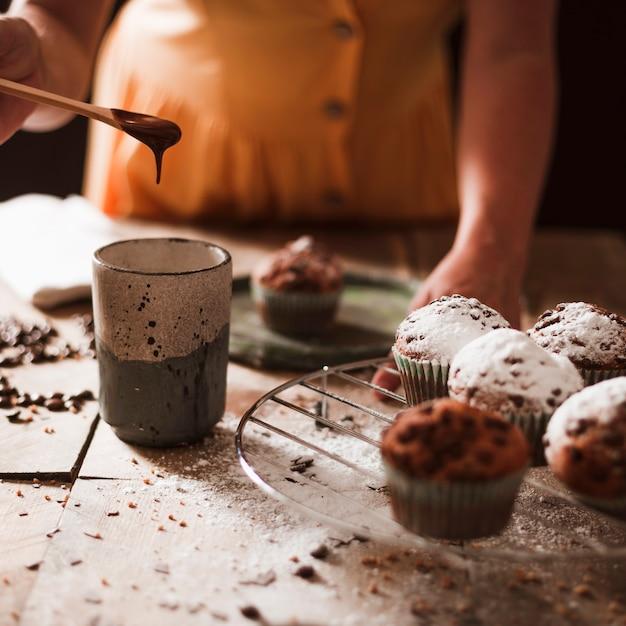 Primo piano di una persona che prepara cioccolato fondente in vetro con cupcakes Foto Gratuite