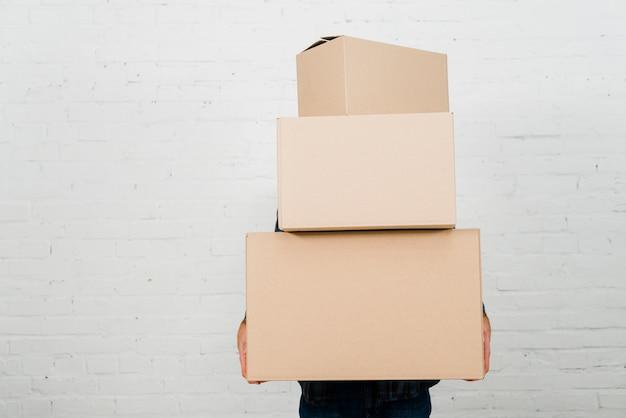 Primo piano di una pila della tenuta della persona di scatole di cartone contro la parete dipinta bianca Foto Gratuite