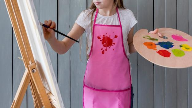 Primo piano di una pittura disponibila della tavolozza della tenuta della ragazza sul cavalletto con il pennello Foto Gratuite