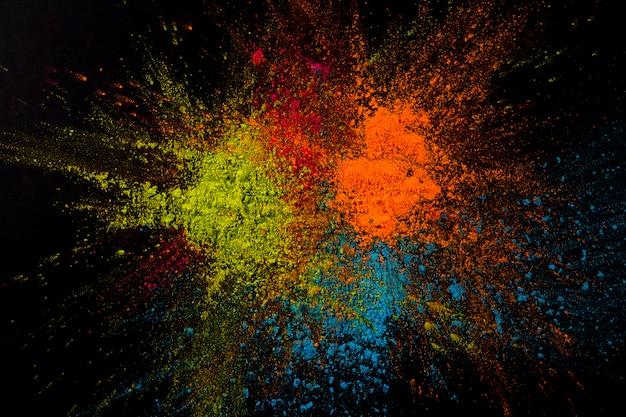 Primo piano di una polvere multicolore che esplode sulla superficie nera Foto Gratuite