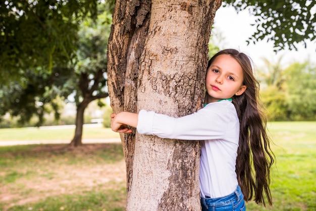 Primo piano di una ragazza adorabile che abbraccia il tronco d'albero Foto Gratuite