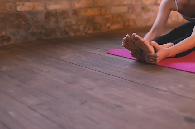 Primo piano di una ragazza che fa un asana che si piega in avanti con le sue mani verso le sue gambe Foto Premium