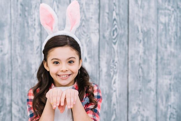 Primo piano di una ragazza che posa come coniglietto contro fondo grigio di legno Foto Gratuite