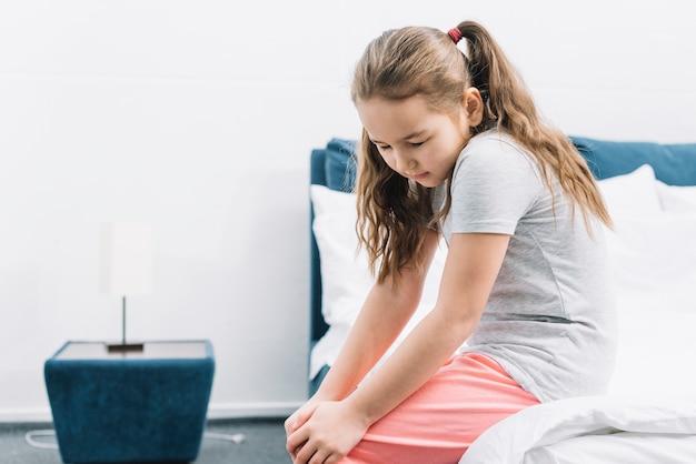 Primo piano di una ragazza seduta sul letto soffre di dolore al ginocchio Foto Gratuite