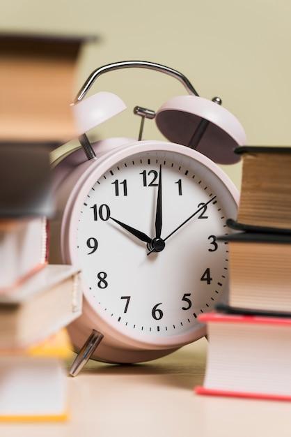 Primo piano di una sveglia e libri impilati Foto Gratuite
