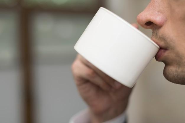 Primo piano di uomo che beve caffè Foto Gratuite