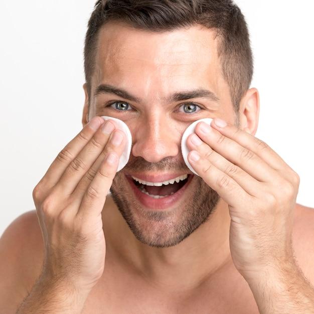 Primo piano di uomo che pulisce il viso con un batuffolo di cotone e sorridente Foto Gratuite