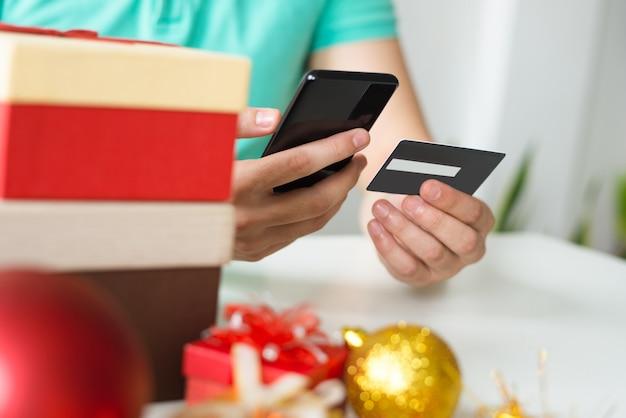 Primo piano di uomo con carta di credito, smartphone e regali di natale Foto Gratuite