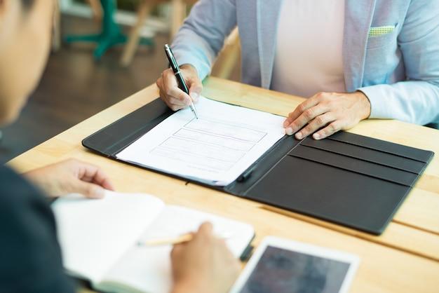 Primo piano di uomo d'affari che si siede al tavolo e compilando il documento Foto Gratuite