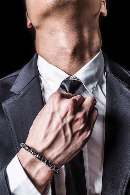 Primo piano di uomo d'affari fissa la sua cravatta Foto Gratuite