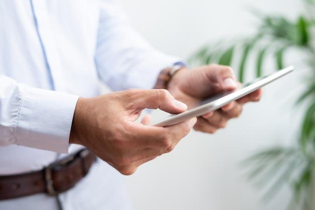 Primo piano di uomo d'affari navigando su tablet pc Foto Gratuite