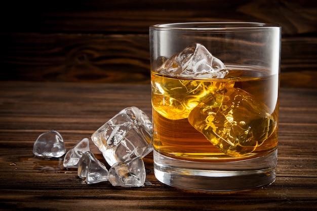 Primo piano di vetro con ghiaccio e whisky Foto Premium