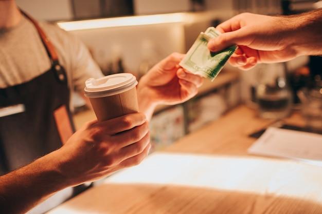 Primo piano e tagliare la vista di una mano barman in possesso di una tazza di caffè e darlo al cliente. allo stesso tempo, il cliente gli sta dando un denaro per pagare l'ordine. Foto Premium