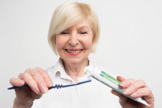 Primo piano e tagliare vuew di una donna che mette un po 'di dentifricio sullo spazzolino da denti. vuole lavarsi i denti. la signora si sta prendendo cura della sua bocca. Foto Premium