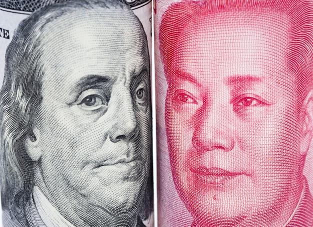 Primo piano faccia a faccia di benjamin franklin e mao tse tung di banconote in dollari statunitensi e cinesi yuan. Foto Premium