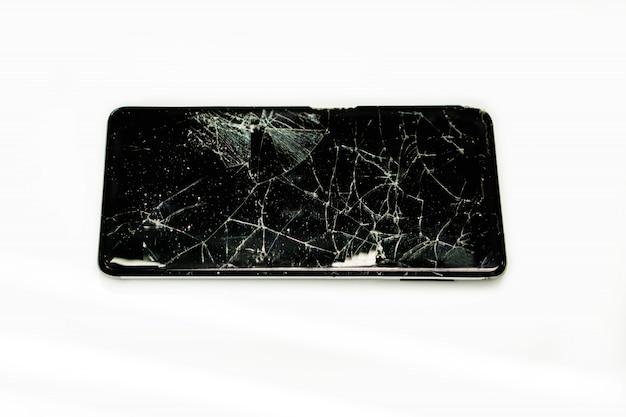 Primo piano rotto e tirato giù dell'isolato nero del telefono cellulare su fondo bianco. Foto Premium