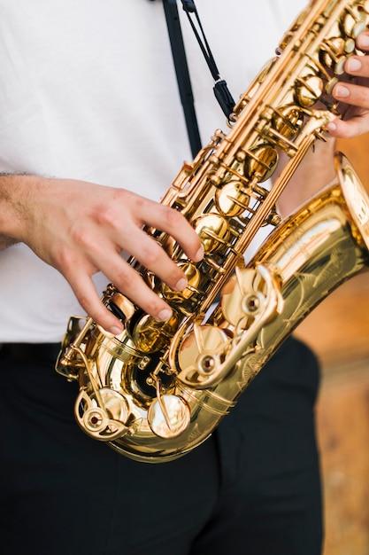 Primo piano sassofono suonato dal sassofonista Foto Gratuite