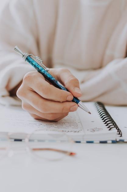 Primo piano selettivo verticale di una scrittura femminile in un taccuino con una penna blu Foto Gratuite