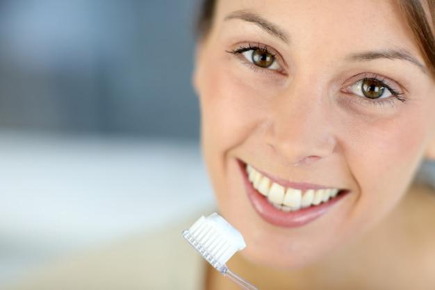 Primo piano sul sorriso toothy della donna che pulisce i suoi denti Foto Premium