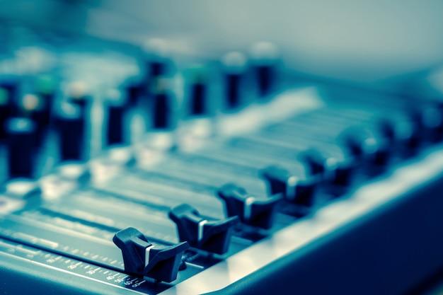 Primo piano una parte del mixer audio, stile cinematografico vintage, concetto di attrezzature musicali Foto Premium