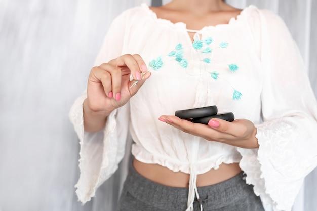 Primo piano: una signora in camicia bianca con una bella delicata manicure rosa tiene due pietre nere per trattamenti benessere e fiori blu. spa e cura della pelle, massaggio. Foto Premium