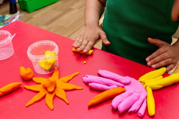 Primo piano variopinto della pasta della muffa delle mani dei bambini. Foto Premium