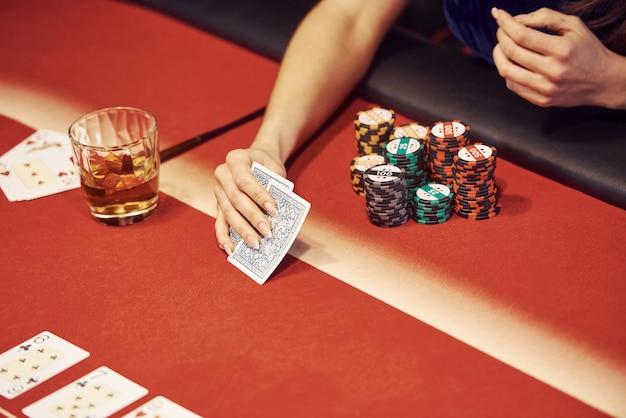 Primo piano vista delle mani della donna. la ragazza gioca a poker al tavolo da casinò Foto Premium