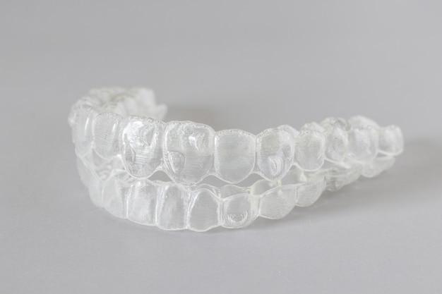 Primo piano vista di parentesi graffe invisibili o fermi invisibili su grigio, nuove apparecchiature ortodontiche Foto Premium