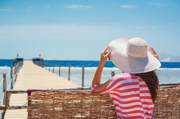 Primo piano vista posteriore della donna in cappello bianco che guarda verso l'oceano blu e il cielo. Foto Premium