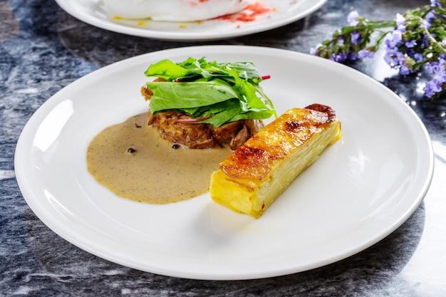 Primo piano vista su gratin di patate in stile perfetto con salsa verde e filetto di tacchino grigliato con spinaci Foto Premium