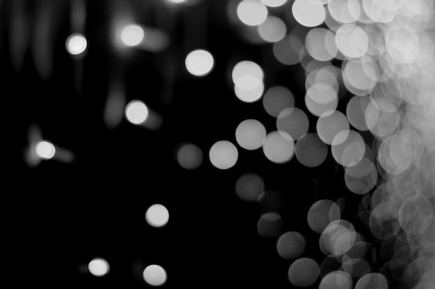 Priorità bassa astratta di bokeh bianco chiaro su una priorità bassa di notte nera. Foto Premium