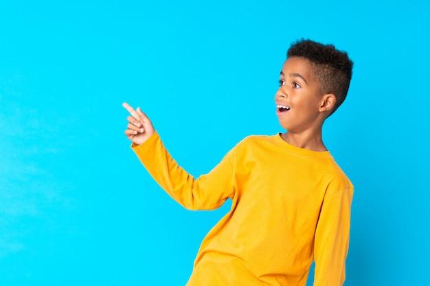 Priorità bassa boyblue dell'afroamericano sorpresa e che indica barretta il lato Foto Premium