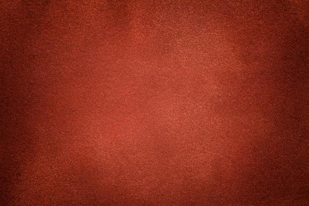 Priorità bassa del primo piano arancione scuro del tessuto della pelle scamosciata. texture vellutata opaca di tessuto nabuk zenzero Foto Premium