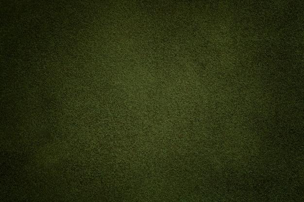 Priorità bassa del primo piano verde scuro del tessuto della pelle scamosciata. texture vellutata opaca di tessuto nabuk verde oliva Foto Premium
