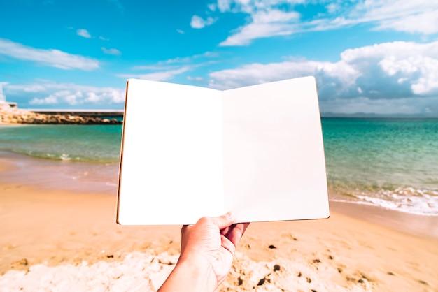 Priorità bassa della spiaggia di estate con un taccuino in bianco Foto Gratuite
