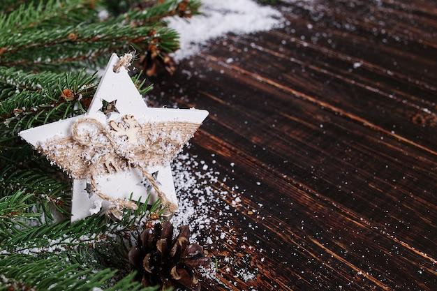 Priorità bassa di concetto di natale, decorazione fatta a mano della stella ed alberi di natale verdi su una tabella di legno, tratteggiata da neve bianca Foto Premium