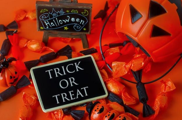 Priorità bassa di halloween - dolcetto o scherzetto sull'etichetta di legno con le caramelle nere ed arancio Foto Premium