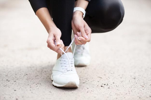 Problema delle scarpe da ginnastica. corridore femminile legando le scarpe preparando per una corsa Foto Premium