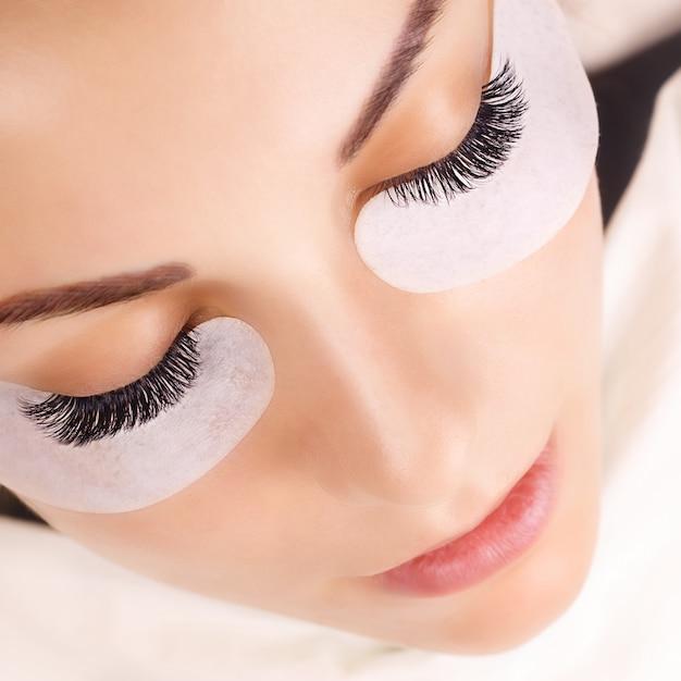 Procedura per l'estensione delle ciglia. occhio di donna con lunghe ciglia. Foto Premium
