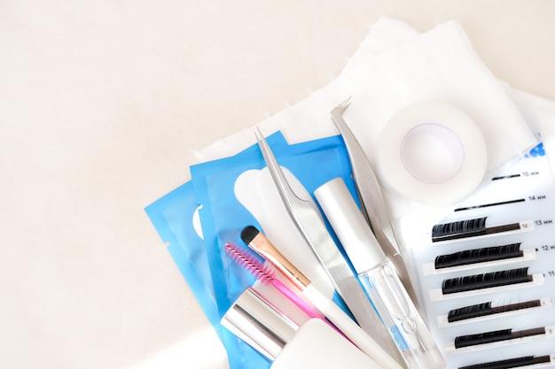 Procedura per l'estensione delle ciglia. utensili. colla, pinzette, pennelli. salone di bellezza, moda e donna compongono il concetto Foto Premium