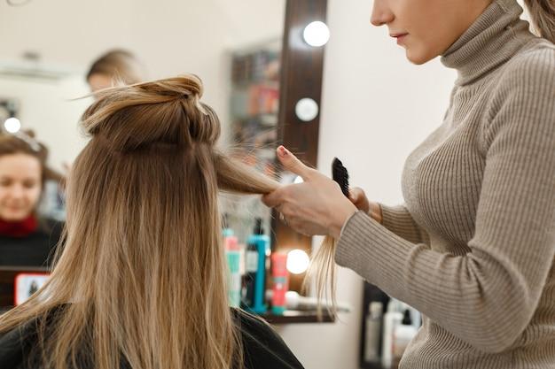 Processo di acconciatura nel salone di parrucchiere. Foto Premium