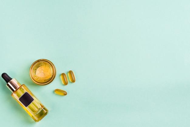 Prodotti naturali di bellezza con crema cosmetica, capsule di gel omega 3 e olio in bottiglie di vetro sul blu Foto Premium