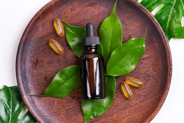 Prodotti naturali di bellezza con le capsule di gel di omega 3 e siero in bottiglie di vetro, foglie verdi sul piatto di legno su bianco Foto Premium