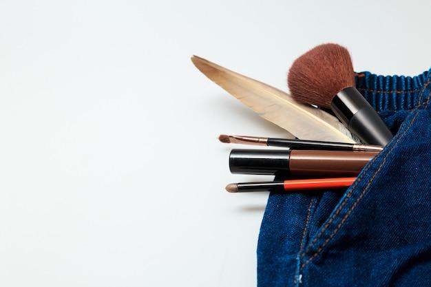 Prodotti per il trucco e prodotti di bellezza cosmetici fuoriusciti da jeans donna Foto Premium