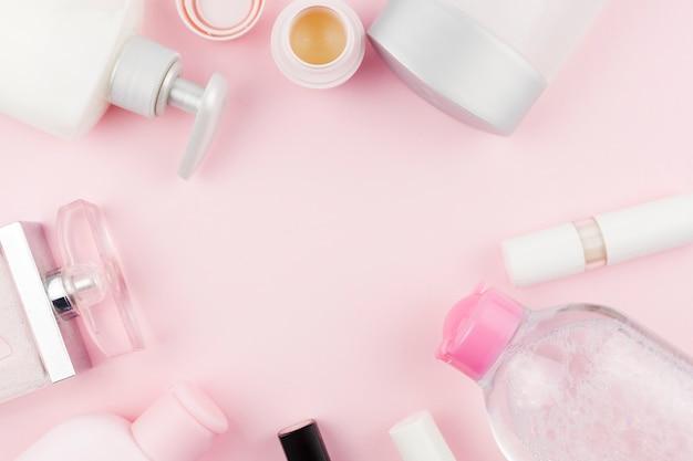 Prodotti per la cura del viso rosa che creano una cornice rotonda Foto Gratuite