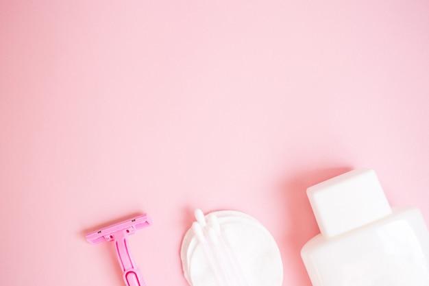 Prodotti per la cura personale. bottiglia bianca, rasoio, tappi per le orecchie, tamponi di cotone su sfondo rosa. c Foto Premium