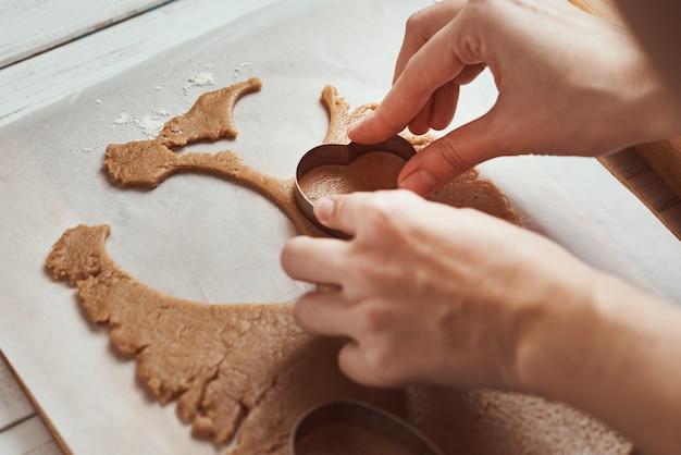 Produrre biscotti di panpepato a forma di cuore per san valentino. taglierina del biscotto di uso della mano della donna. concetto di cibo per le vacanze Foto Premium